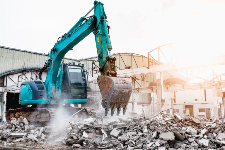 Excavators machine in construction site demolishing existing building